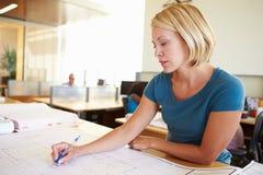 Het vrouwelijke Bureau van Architectenstudying plans in Stock Afbeeldingen