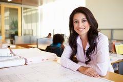 Het vrouwelijke Bureau van Architectenstudying plans in Royalty-vrije Stock Fotografie