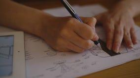 Het vrouwelijke Bureau van Architectenstudying plans in bij bureau stock videobeelden