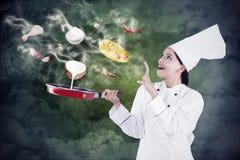 Het vrouwelijke chef-kok koken met magisch Royalty-vrije Stock Foto's