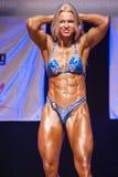 Het vrouwelijke cijfermodel buigt haar spieren en toont haar lichaamsbouw Stock Foto