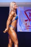 Het vrouwelijke cijfermodel buigt haar spieren en toont haar lichaamsbouw Royalty-vrije Stock Fotografie