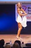 Het vrouwelijke cijfermodel buigt haar spieren en toont haar lichaamsbouw Stock Afbeelding