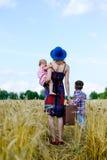 Het vrouwelijke dragen valize met twee kinderen status Stock Afbeeldingen