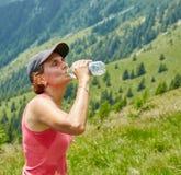 Het vrouwelijke drinkwater van de sleepagent stock fotografie