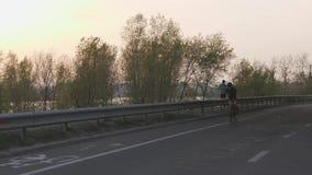 Het vrouwelijke fietser berijden naar camera bij zonsondergang Cinematic het cirkelen concept stock video