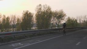Het vrouwelijke fietser berijden naar camera bij zonsondergang Cinematic het cirkelen concept Langzame Motie stock videobeelden