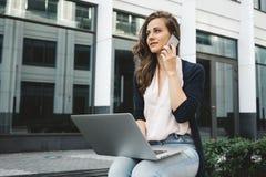 Het vrouwelijke freelance werken met laptop aan straat in bedrijfsdistrict en bespreekt het werk telefonisch met klant stock foto's