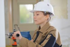Het vrouwelijke gat van bouwersboren in muur stock foto
