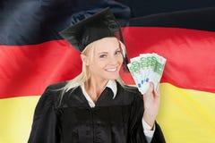 Het vrouwelijke gediplomeerde geld van de studentenholding royalty-vrije stock foto