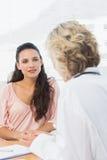 Het vrouwelijke geduldige luisteren aan arts met concentratie stock afbeelding