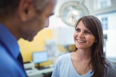 Het vrouwelijke geduldige in wisselwerking staan met arts tijdens bezoek stock foto's