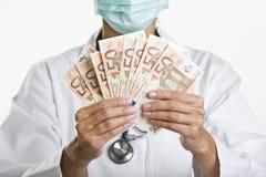 Het vrouwelijke geld van de artsenholding Royalty-vrije Stock Foto's