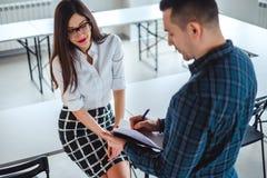 Het vrouwelijke glimlachen terwijl haar werkgever nota's neemt stock fotografie