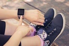 Het vrouwelijke hand drukken de knoop op slim horloge stock fotografie