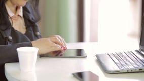 Het vrouwelijke handen genomen close-up werkt aan een tablet, naast het is laptop en een beschikbaar glas koffie stock videobeelden