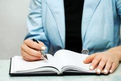 Het vrouwelijke handen schrijven. Stock Afbeeldingen