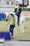 Het vrouwelijke jockey berijden in een blauw kostuum op een wit paard Internationale Paardtentoonstelling Moskou Royalty-vrije Stock Fotografie
