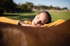 Het vrouwelijke jockey ontspannen op paard bij schuur royalty-vrije stock foto's
