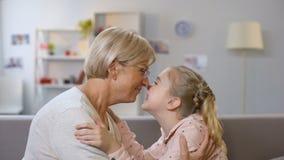 Het vrouwelijke jong geitje en oma nuzzling, familiegeneraties, liefdeverbinding, nabijheid stock video