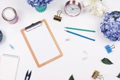 Het vrouwelijke kader van de bureauwerkruimte met schoonheidsregeling van boekethydrangea hortensia's, klembord, koffiekop, klemm royalty-vrije stock foto's