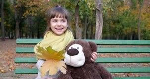 Het vrouwelijke kind stellen met teddybeer en gele bladeren in handen bij camera op achtergrond de herfstpark stock footage