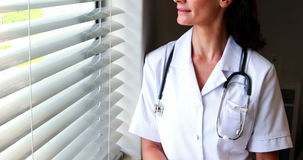 Het vrouwelijke klembord van de artsenholding en het kijken door venster stock footage