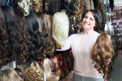 Het vrouwelijke kopen bij de verschillende uitbreidingen van het kleurenhaar stock foto's