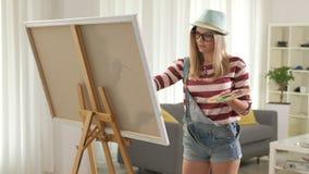 Het vrouwelijke kunstenaar schilderen op een canvas stock videobeelden