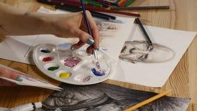 Het vrouwelijke kunstwerk van de kunstenaarstekening thuis met borstel stock video