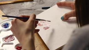 Het vrouwelijke kunstwerk van de kunstenaarstekening thuis met borstel stock footage