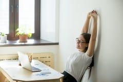 Het vrouwelijke manager uitrekken zich omhoog op haar stoel royalty-vrije stock afbeelding