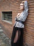 Het vrouwelijke model stellen die tegen bakstenen muur leunen Stock Foto