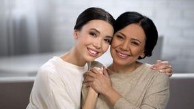 Het vrouwelijke omhelzen, die camera, verfrist gezicht na de producten van de huidzorg onderzoeken royalty-vrije stock foto