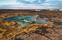 Het vrouwelijke ongehaaste drijven in een rotspool door de oceaan royalty-vrije stock afbeeldingen