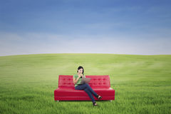 Het vrouwelijke ontspannen op rode bank openlucht Royalty-vrije Stock Afbeeldingen