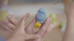 Het vrouwelijke paasei van de handholding terwijl meisje die onhandig op het schilderen die een kleine borstel dicht uitputten Vo stock videobeelden