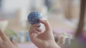 Het vrouwelijke paasei van de handholding terwijl meisje die onhandig op het schilderen die een kleine borstel dicht uitputten Vo stock video