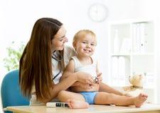 Het vrouwelijke pediater onderzoeken van kind met stock afbeeldingen