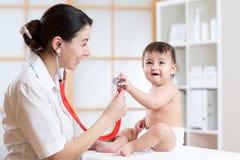 Het vrouwelijke pediater onderzoeken van peuterjong geitje met stethoscoop stock foto