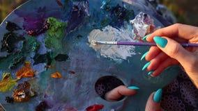 Het vrouwelijke penseel van de schildersholding over palet stock videobeelden