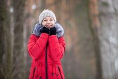 Het vrouwelijke portret in openlucht in rood de winterjasje, kijkt in camera royalty-vrije stock fotografie