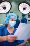 Het vrouwelijke rapport van de chirurgenlezing in verrichtingsruimte Royalty-vrije Stock Afbeelding
