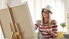 Het vrouwelijke schilder schilderen op een canvas stock video
