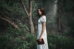 Het vrouwelijke slachtoffer in witte kleding houdt boek in hand royalty-vrije stock fotografie
