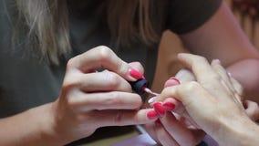 Het vrouwelijke spijker oppoetsen Roze vernis Sluit omhoog mening Duimspijker het schilderen stock footage