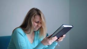 Het vrouwelijke student bestuderen en het lezen in een bibliotheek maar hebben een harde tijd begrijpend het materiaal stock video