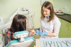 Het vrouwelijke tandarts werken bij tandkliniek met wijfje patien royalty-vrije stock foto's