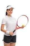 Het vrouwelijke tennisspeler stellen met bal en racket Royalty-vrije Stock Foto's