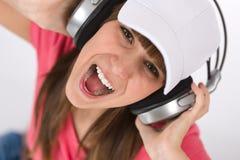 Het vrouwelijke tiener zingen met hoofdtelefoons Stock Afbeeldingen